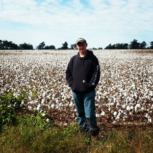 James in front of a field of cotton. Cotton as far as the eye could see.